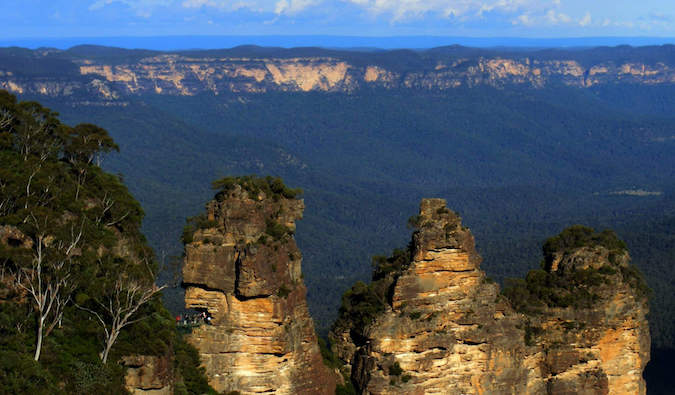 The three sisters in the Blue Mountains of Australia with blue sky and lush background