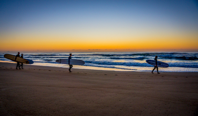 Surfers walking down the beach at sunset with their surfboards