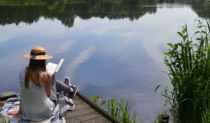 girl sitting outdoors reading travel books