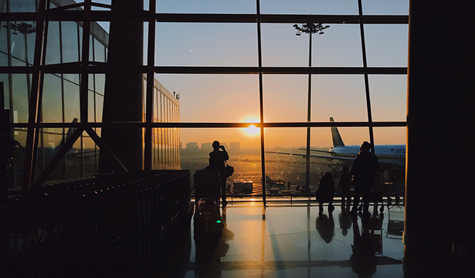 a man gazing out at the airplanes in an airport