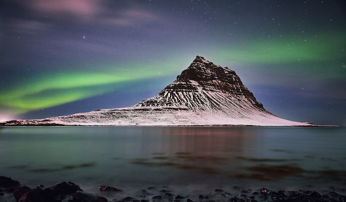 a mountain peak in Iceland under the Northern Lights