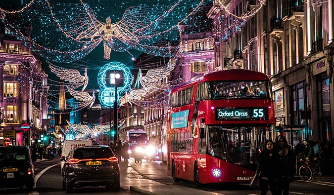 a red London bus with Christmas lights at night
