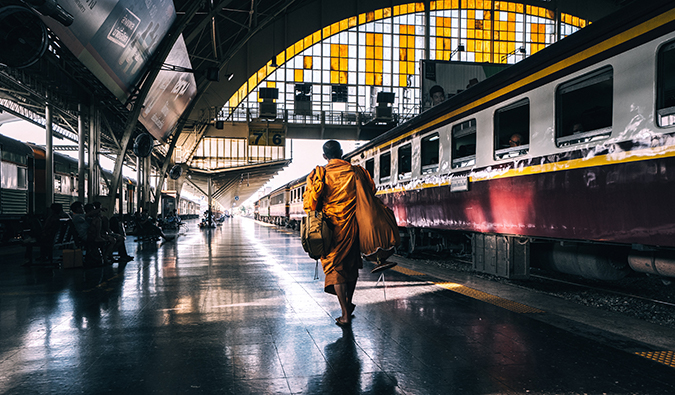 a monk in orange robes boarding a plane in Asia