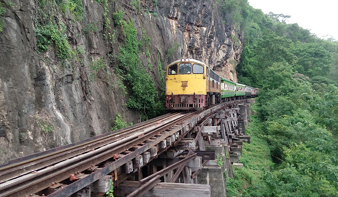 a train hugging the cliff side in Kanchanaburi, Thailand