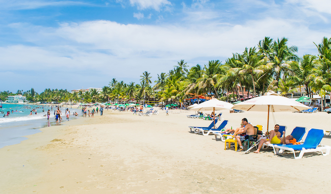 people lounging in beach chairs on a crowded beach