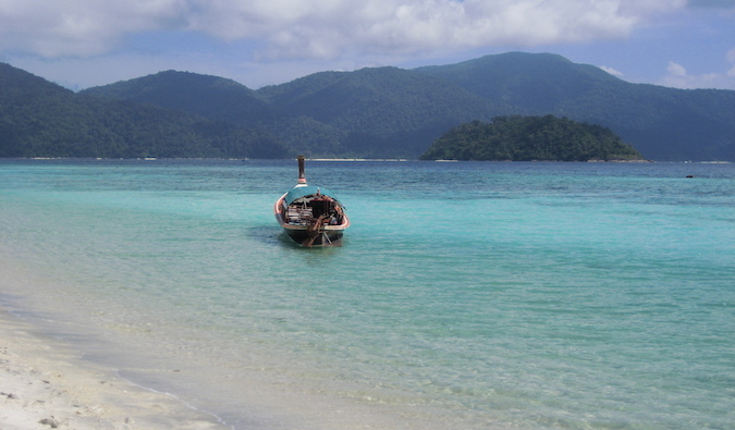 boat floating in the gorgeous blue waters of Ko Lipe