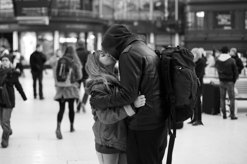 loving black and white photo of backpackers kissing at the transportation hub while traveling
