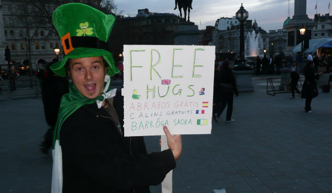 Benny Lewis wearing a leprechaun hat and holding a sign saying FREE HUGS in multiple languages