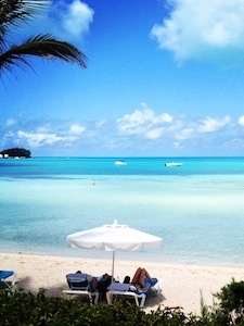 Bermuda beaches with white lawn chairs and umbrella with the clear blue water in the background
