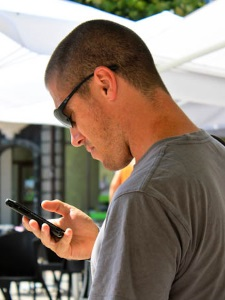 Dave Dean playing with his smartphone abroad