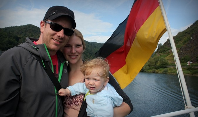 Traveling family of three posing with a German flag
