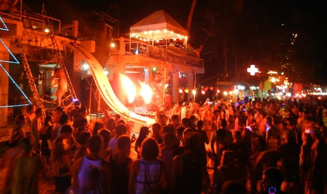 Crazy fire sign and young backpacking tourist crowds in Thailand at the Full Moon Party