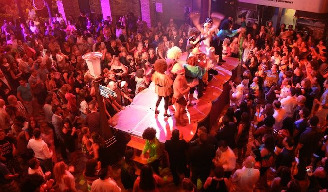Packed dance floor on a cruiseship, women dancing on tables