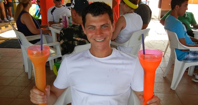 Nomadic Matt holding drinks and enjoying cruise life