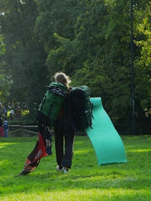 Budget traveler walking through a park carrying a backpack