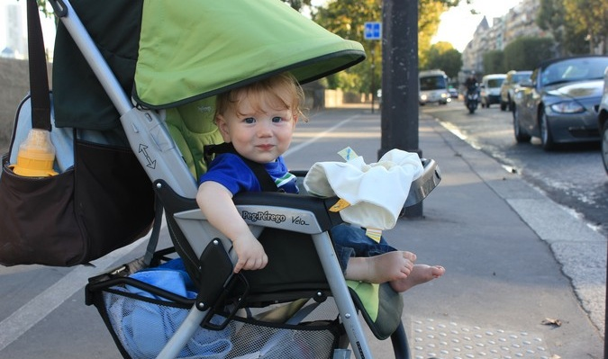 cute baby smiling at camera in stroller while traveling
