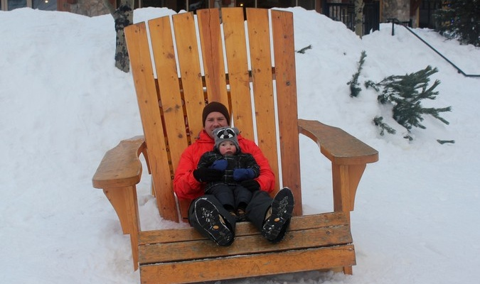 dad and son posing in an oversized chair while sightseeing in the snow