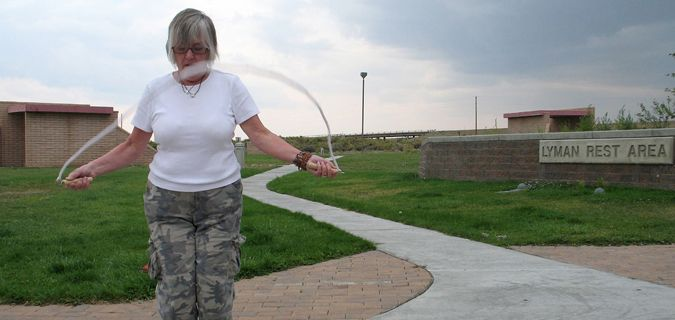 Older woman jumping rope and exercising while on the road
