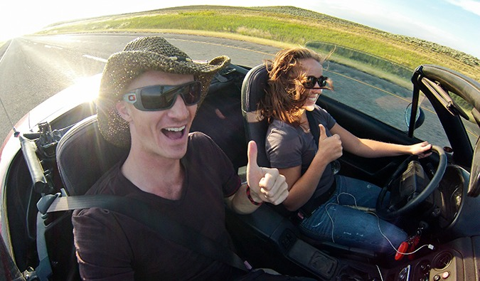 Male hitchhiker with a female driver riding along the road in a top-down convertible