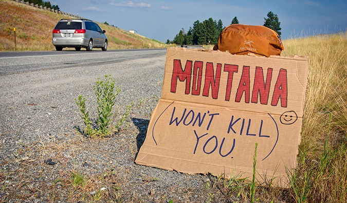 Hitchhiknig sign saying that Montana Won't Kill You