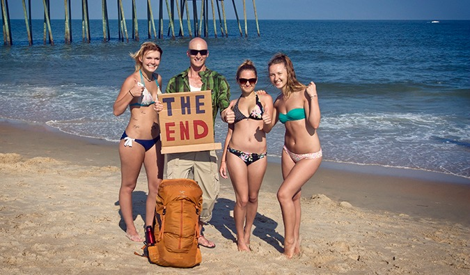 Man standing on the beach with 3 girls in bikinis and a cardboard hitchhiking sign saying THE END