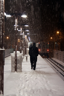 Man walking in the snow in a city