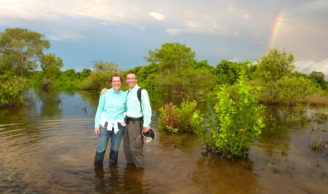 older couple traveling in a developing country with a rainbow in the background