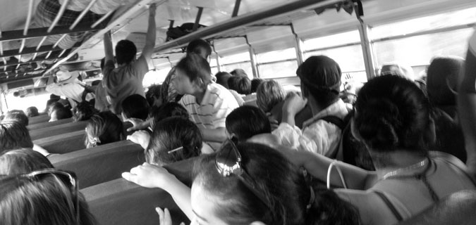 Black and white photo of people on a bus in Africa