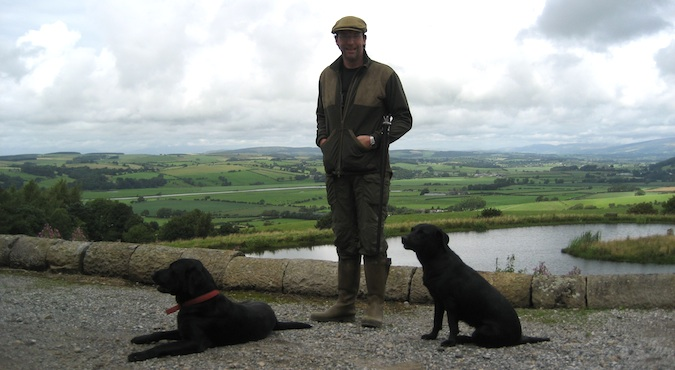 A British man with two dogs in from of the Lake in England