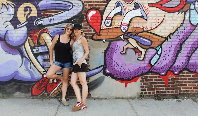 couple leaning against wall with street art