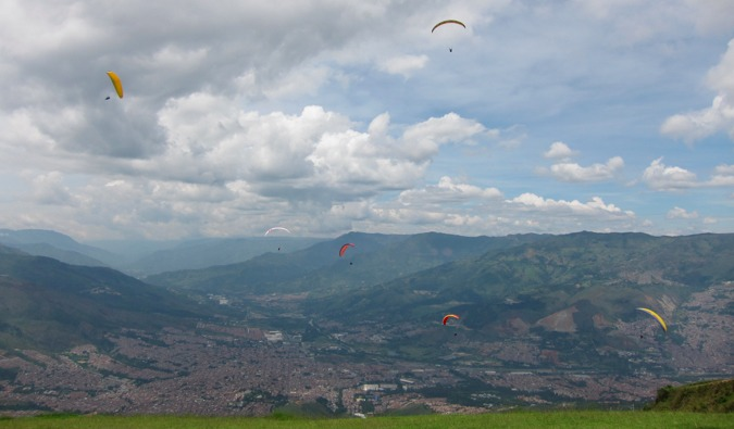 Five paragliders gliding over the city of Medellin