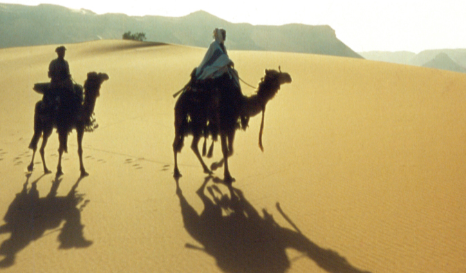 Lawrence of Arabia riding camel back through the desert in this classic film