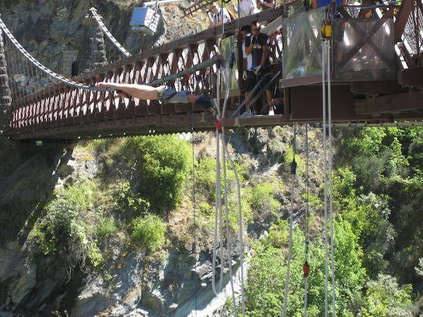 A girl bungy jumping off a bridge in New Zealand