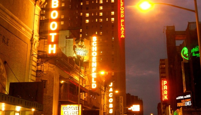 Neon signs light up the hazy streets of Manhattan near the theater district