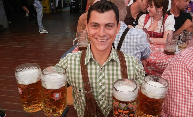Matt Kepnes posing with 4 huge beers at Oktoberfest in Germany