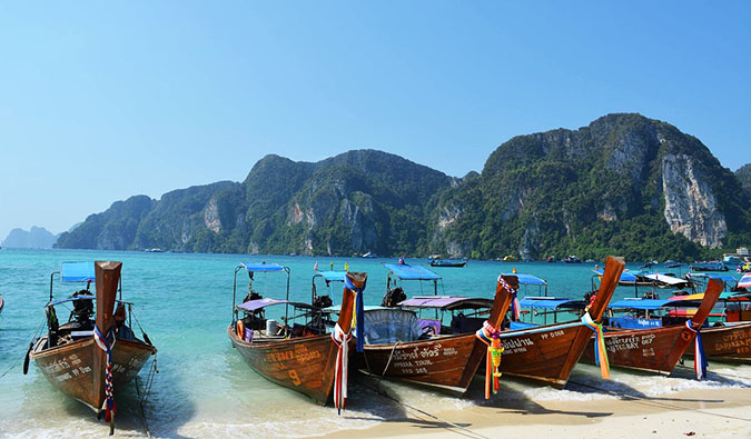 The classic long-tail boats of Thailand all lined up on a beautiful beach in Ko Phi Phi