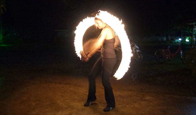 A fire dancer in Thailand spinning fire on the beach at night on Ko Phi Phi