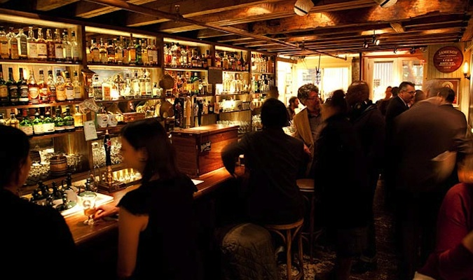 People drinking at a dimly lit prohibition bar called The Dead Rabbit