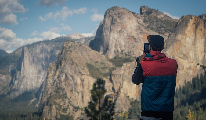 traveler taking photos of beautiful mountain range