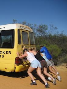 travelers pushing a bus