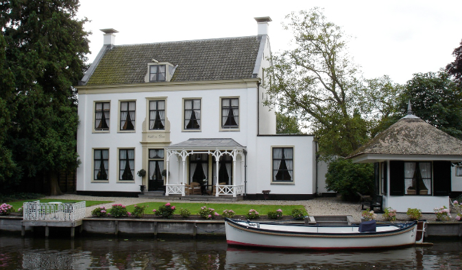 White home on the canal of Utrecht, with canoe