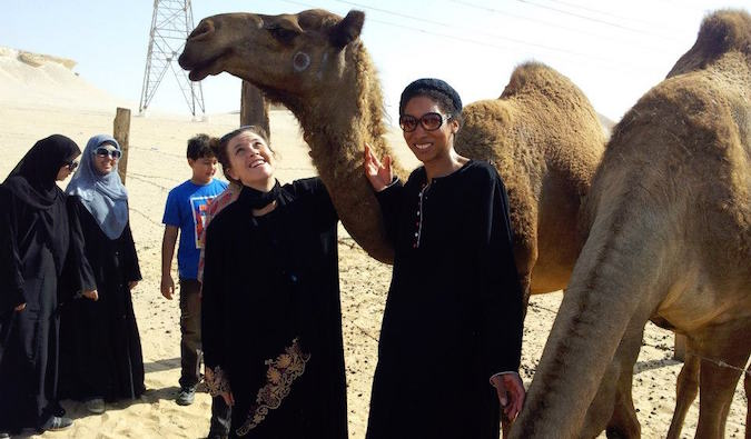Woman teaching in Saudi Arabia at a camel farm wearing Middle Eastern clothes
