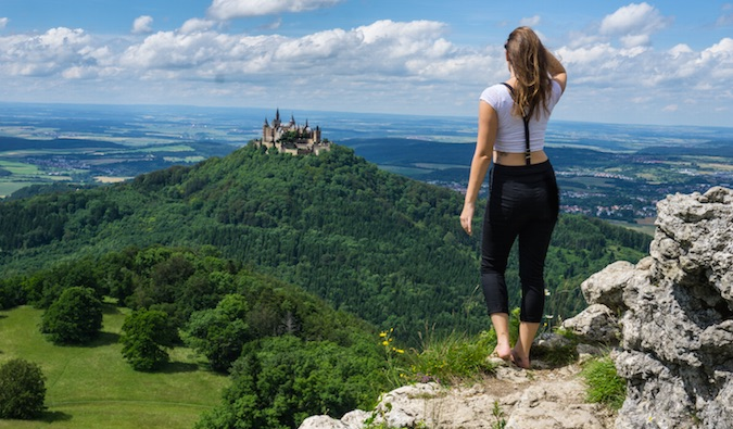 Kristin looking at a beautiful castle in the distance atop a lush green hill