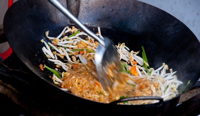Pad thai food in a pan being stirred