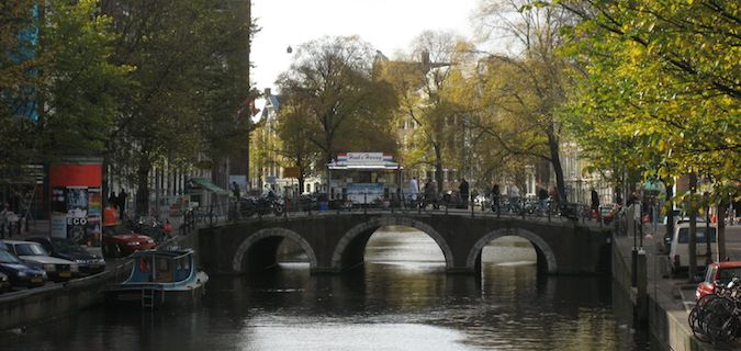 Bridge over the canal in Amsterdam, surrounded by trees