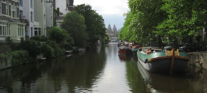 Perspective view of Amsterdam's canals with boats in it