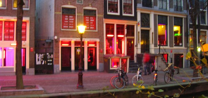 The Red Light District in Amsterdam with red lights shining from the shop windows