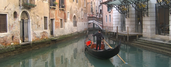 Taking a gondola ride through the canals of Venice