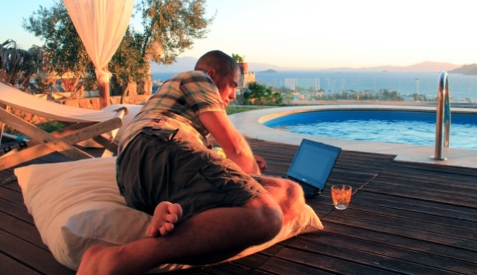 David Dean of too many adapters using a computer at sunset by a swimming pool on vacation
