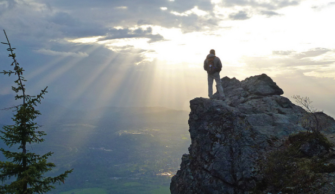 Traveling man standing on a mountain after hiking it